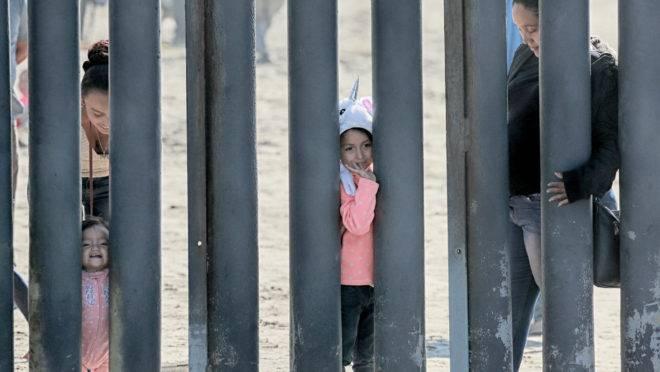 Imigrantes na fronteira do México com os EUA, em San Ysidro, Califórnia