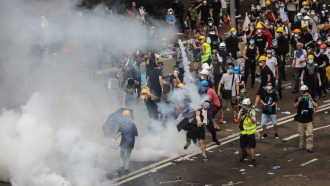 Manifestante joga uma bomba de gás lacrimogêneo disparada pela polícia durante uma manifestação em Hong Kong