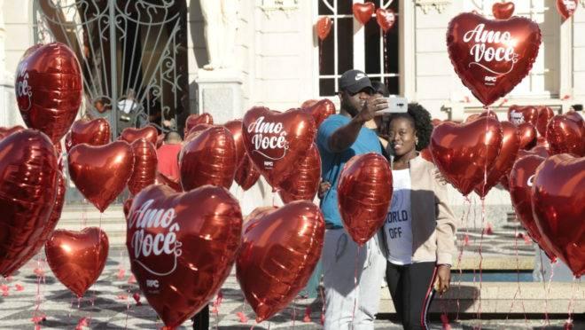 Casal tirando foto em meio a balões em forma de coração