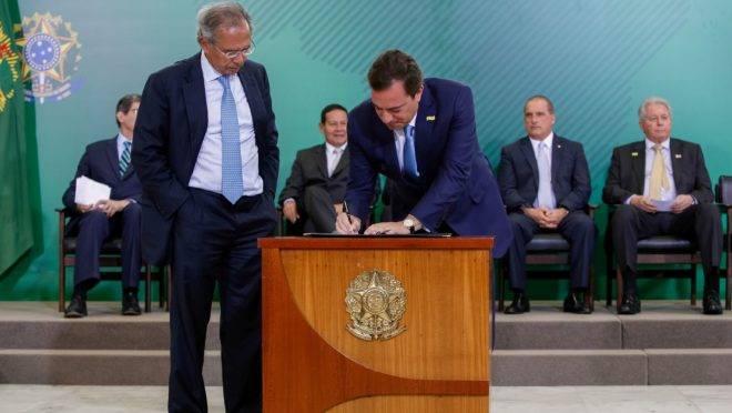 O ministro da Economia, Paulo Guedes, e o presidente da Caixa, Pedro Guimarães, em foto de janeiro de 2019: banco estatal vai devolver dinheiro que a União emprestou.
