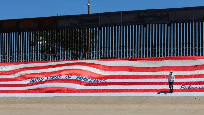 Faixa de protesto às políticas americanas de imigração, colocada no muro de fronteira com o México, perto do Rio Grande.