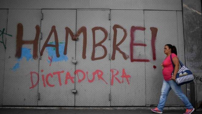 """Mulher passa por pichação que diz """"Fome e Ditadura"""" em Caracas, 13 de junho"""