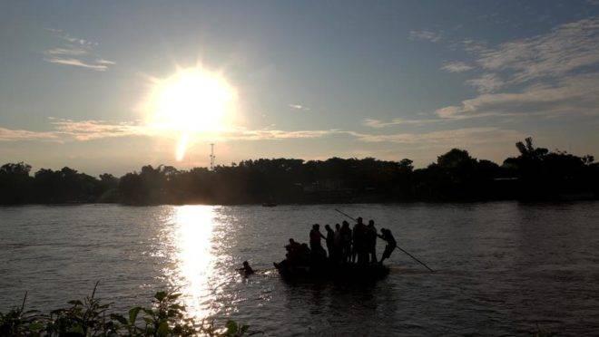 Migrantes e residentes usam um bote improvisado para atravessar ilegalmente o Rio Suchiate, de Tecum Uman, Guatemala, para Ciudad Hidalgo, México, em 14 de junho