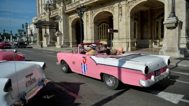 Taxista particular em um antigo carro americano leva os turistas nas ruas de Havana