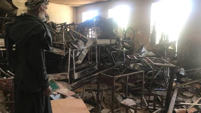 Um segurança olha carteiras danificadas e destroços no interior da escola para meninas Sher Ali Khan em Naw Deh, na província de Farah, Afeganistão, em abril de 2019. Dois ataques a bomba no Afeganistão renovaram os temores de uma volta da repressão caso o Talibã se torne parte de um governo futuro