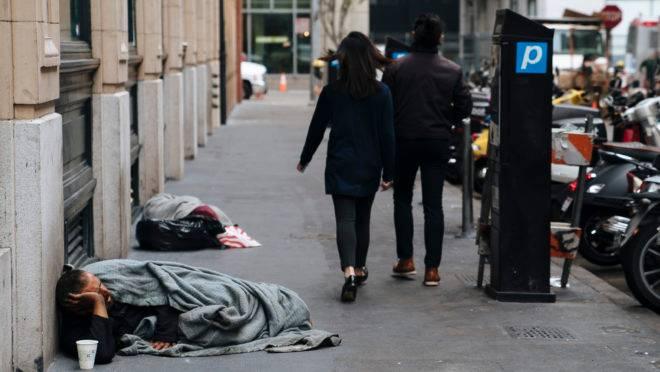Pedestres caminham por moradores de rua que dormem nas calçadas de San Francisco.