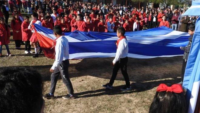 Alunos da escola pública argentina levando a bandeira de Cuba para ser hasteada. Foto: Facebook | Reprodução.