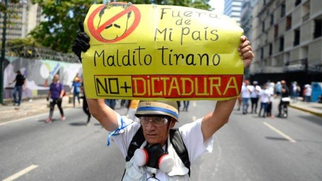 Manifestante da oposição segura um cartaz contra o ditador venezuelano, Nicolas Maduro