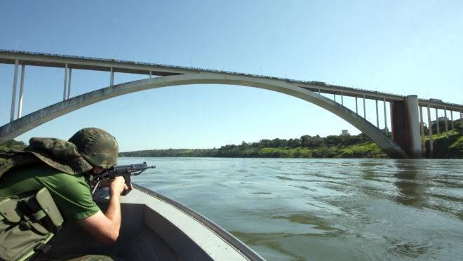 Imagem exibe soldado do Exército com carabina fazendo patrulha das margens do Rio Paraná em Foz do Iguaçu, nas proximidades da Ponte da Amizade, na fronteira com o Paraguai.