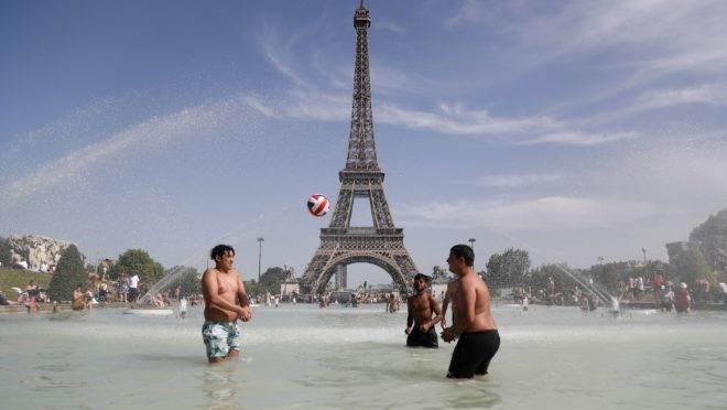 Pessoas se banham em frente à Torre Eiffrel