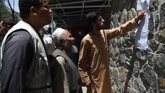Afegãos conferem uma lista com os nomes das vítimas de um atentado do Talibã no centro de Cabul, em frente a um hospital de uma organização humanitária italiana