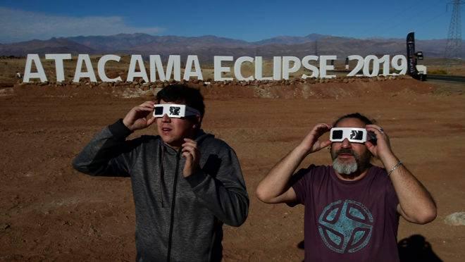 Turistas experimentam óculos especiais para assistir a um eclipse solar total em 2 de julho, no deserto de Atacama