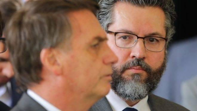 O ministro das Relações Exteriores, Ernesto Araújo, olha para o presidente Jair Bolsonaro
