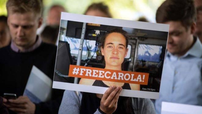 Manifestantes seguram cartaz de apoio à capitã alemã Carola Rackete, em 2 de julho