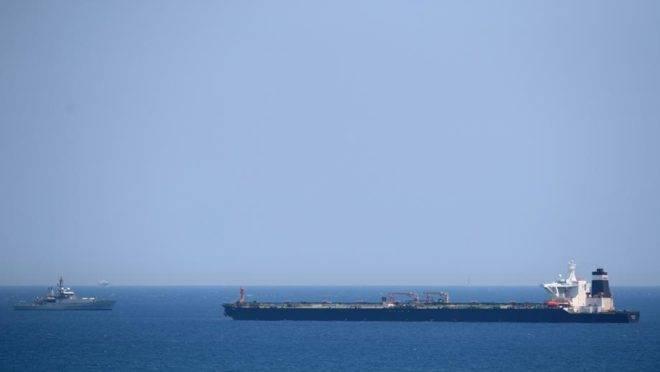 Um navio da Marinha Real Britânica (à esquerda) em patrulha perto do supertanque Grace 1, suspeito de transportar petróleo cru para a Síria, violando sanções da UE, após ter sido detido na costa de Gibraltar, 4 de julho