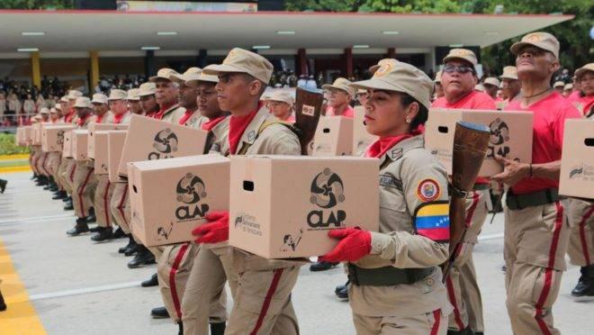 Membros da milícia venezuelana seguram caixas dos Comitês Locais de Abastecimento e Produção (CLAP) ao desfilar diante de Nicolás Maduro durante parada militar no dia da Independência da Venezuela, em Caracas, 5 de julho