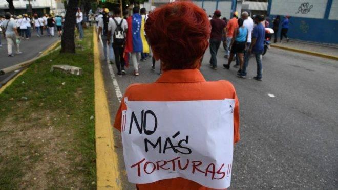 """Mulher com cartaz que diz """"Não mais tortura"""" participa de marcha contra o regime de Maduro em Caracas, 5 de julho"""