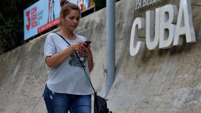 Mulher usa telefone celular para se conectar à internet em Havana, em dezembro de 2018, quando a internet móvel começou a funcionar no país