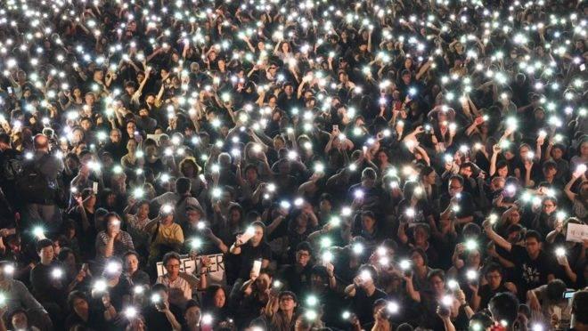 Manifestantes seguram celulares durante marcha organizada por mães de Hong Kong em apoio aos manifestantes que protestam contra o projeto de lei que permitiria a extradição para a China