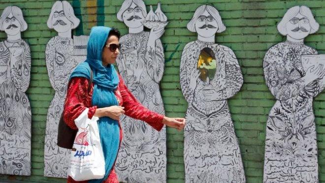 Mulher caminha por uma rua de Teerã, 8 de julho