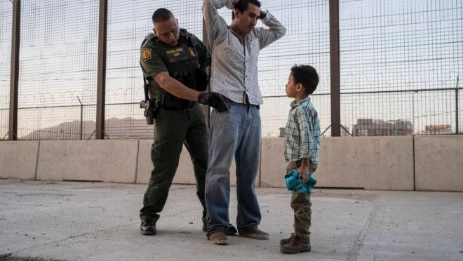 Imigrante é revistado é revistado por um agente da Agência de Alfândega e Proteção de Fronteira dos EUA