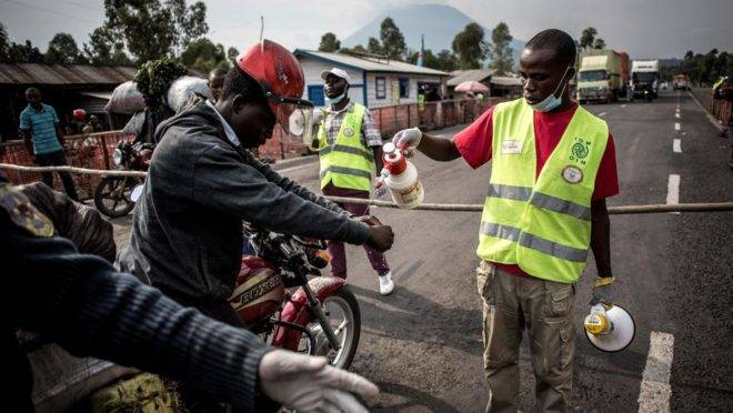 Funcionário lava as mãos de motorista de táxi em estação de controle na estrada entre Butembo e Goma, na República Democrática do Congo, 16 de julho