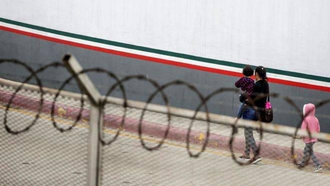 Uma migrante centro-americana e seus filhos em frente ao ponto de entrada em El Chaparral, em Tijuana, no estado mexicano de Baja California, em 17 de julho de 2019
