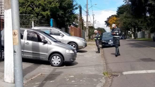 Agentes da Setran multam os carros de revendas estacionados na calçada no bairro Novo Mundo.