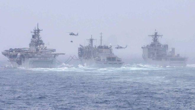 O navio anfíbio de assalto USS Boxer, à esquerda, e o USS Harpers Ferry, à direita, conduzem um reabastecimento no mar com o navio de apoio de combate rápido USNS Arctic. Eles estão posicionados na área de operação da 5a Frota dos EUA