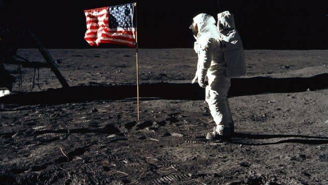 Astronauta Buzz Aldrin posa para uma fotografia ao lado da bandeira dos Estados Unidos durante atividade extraveicular da Apollo 11 na superfície da Lua. O módulo lunar está à esquerda e as pegadas dos astronautas estão visíveis