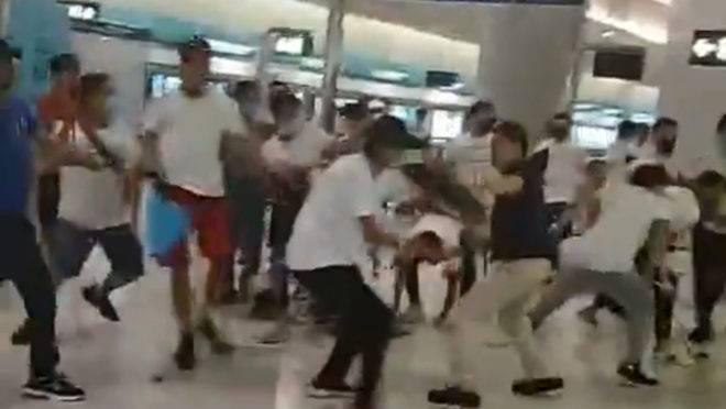 Homens vestindo camisetas brancas entram em confronto com manifestantes pró-democracia na estação Yuen Long em Hong Kong.