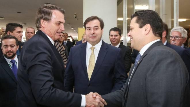 O presidente Jair Bolsonaro aperta a mão do presidente do Senado, Davi Alcolumbre. Ao fundo, o presidente da Câmara, Rodrigo Maia