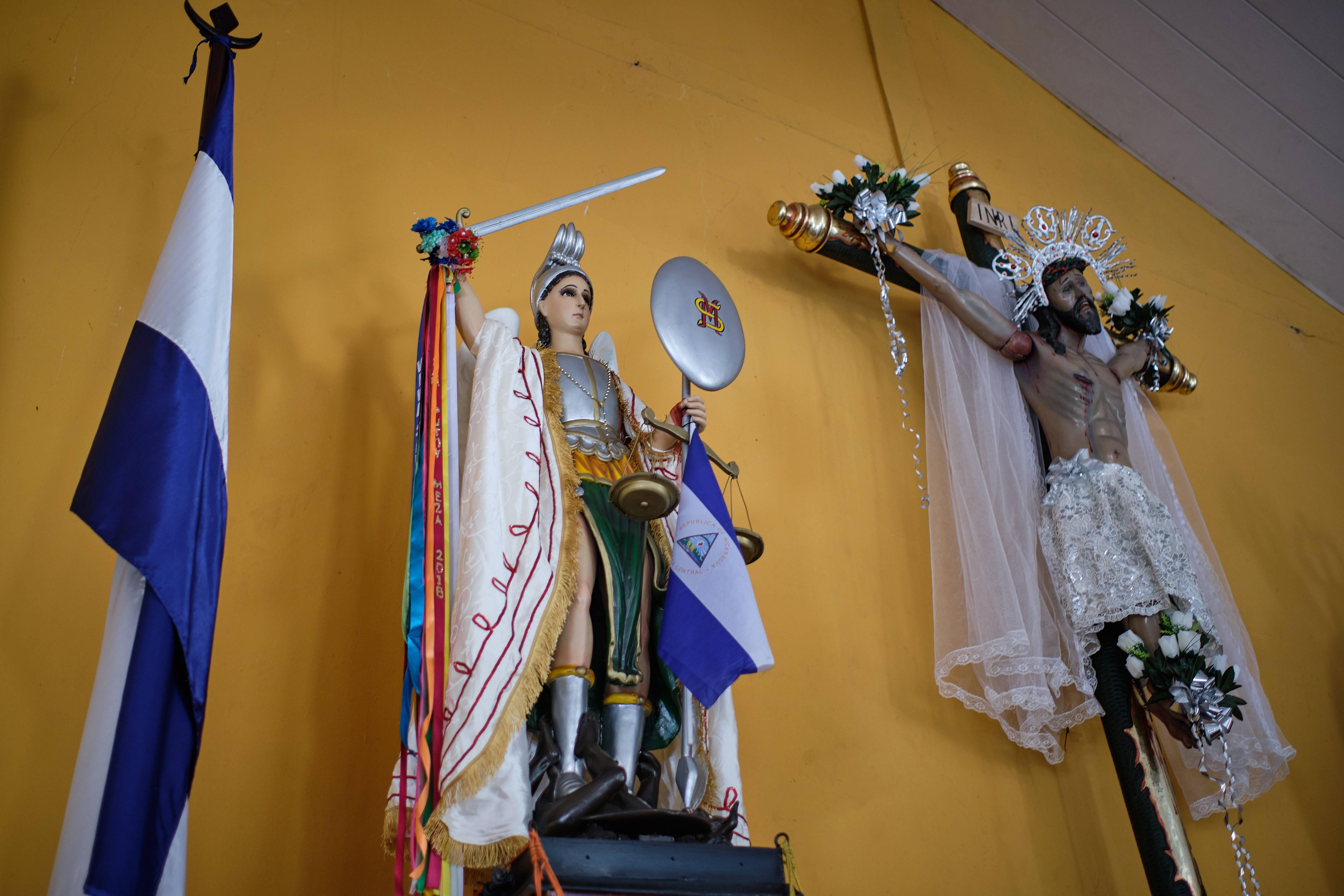 Estátuas de São Miguel são adornadas com a bandeira da Nicarágua, que se tornou um símbolo de resistência ao governo de Ortega | Foto: Carlos Herrera/Washington Post