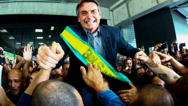Jair Bolsonaro é carregado por apoiadores no Aeroporto Afonso Pena, em Curitiba, em março de 2018.