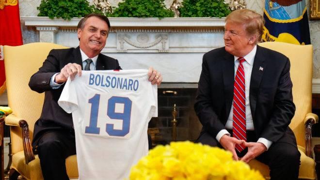 Donald Trump entrega camisa  personalizada da seleção de futebol dos EUA com o nome de Bolsonaro.