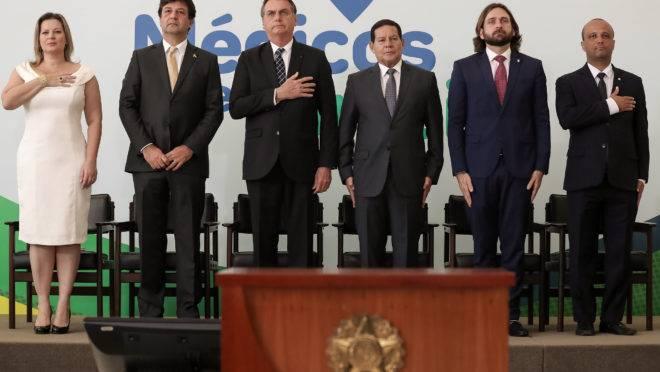 Bolsonaro e outras autoridades durante a execução do hino brasileiro na cerimônia de lançamento do programa Médicos pelo Brasil.