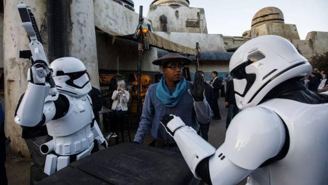Atores em roupas de tropa interestelar interagem com frequentador do parque Star Wars, em Anaheim, Califórnia.