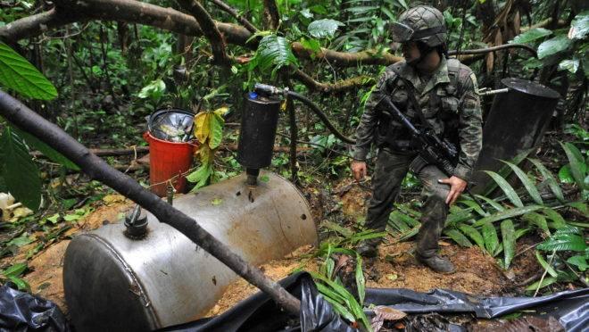 Soldado colombiano encontra tanque para armazenagem de cocaína em um laboratório de refino da Farc no meio da selva.