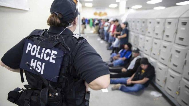 Agente do departamento de Investigações de Segurança Interna vigia suspeitos imigrantes ilegais em 7 de agosto de 2019. Agentes detiveram cerca de 680 imigrantes que trabalhavam em sete fábricas em cidades do Mississippi supostamente de maneira ilegal