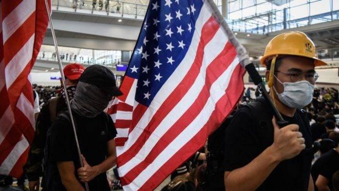 Manifestantes pró-democracia em Hong Kong levantam bandeiras dos Estados Unidos no aeroporto internacional da cidade.