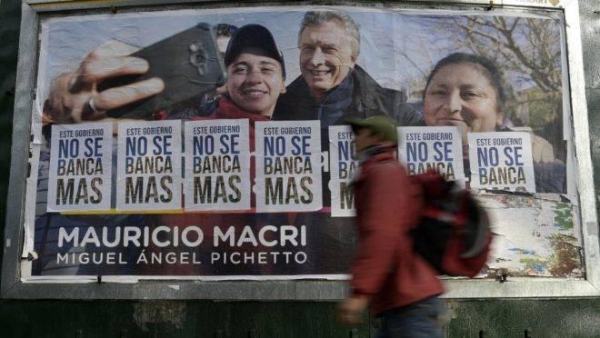 Outdoor de Mauricio Macri parcialmente coberto por cartazes com slogans contra o governo argentino, em Buenos Aires: atual presidente saiu derrotado das eleições primárias da Argentina.