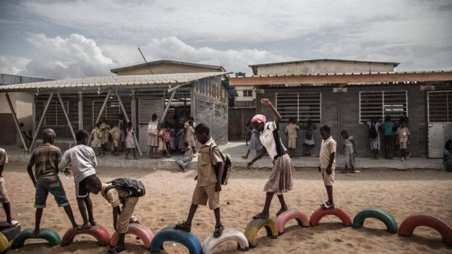 Estudantes brincam em pneus pintados em frente à escola, onde os prédios são construídos com tijolos de plástico, em Abidjan, Costa do Marfim, 24 de junho de 2019