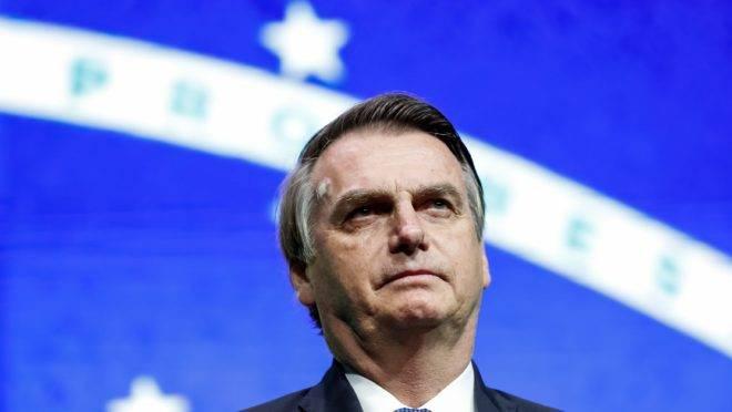 Bolsonaro na frente da bandeira do Brasil.