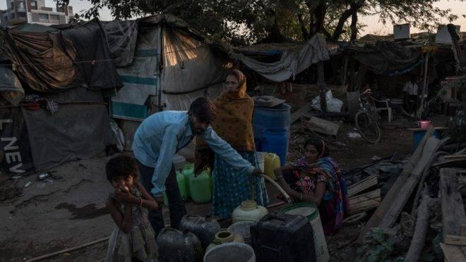 Moradores coletam água do lado de fora de uma barraca de chá em Ahmedabad, estado de Gujarat, Índia, em 24 de novembro de 2018 | REBECCA CONWAY/NYT