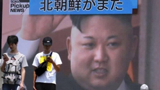 Pedestre passam por uma tela em Tóquio que noticia o lançamento de mísseis pela Coreia do Norte no dia 10 de agosto de 2019