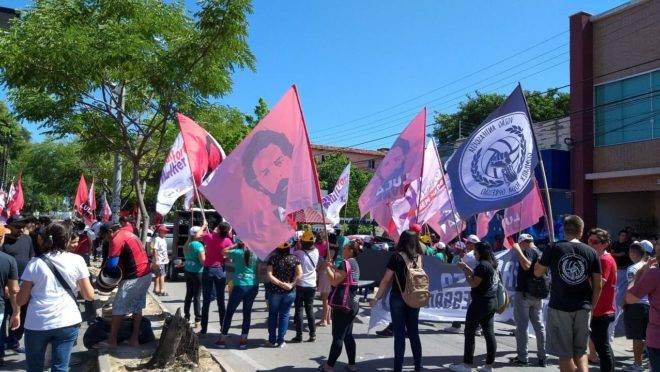 Manifestantes levantam bandeiras com a imagem do ex-presidente Luiz Inácio Lula da Silva.