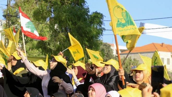 Mulheres apoiadoras do movimento militante xiita libanês Hezbollah agitam bandeiras do grupo em uma comemoração aos 13 anos do fim da guerra com Israel em 2006, na cidade do sul do Líbano Bint Jbeil, 16 de agosto de 2019