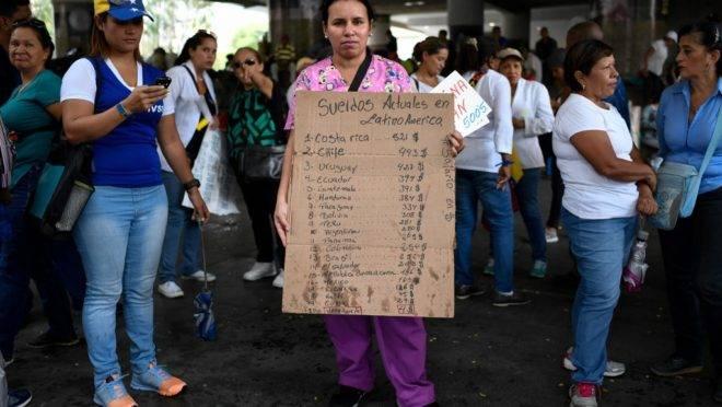 Uma enfermeira venezuelana segura um cartaz com a comparação de salários de enfermeiros na América Latina durante protesto por melhores salários e contra a falta de medicamentos e suprimentos em hospitais, em Caracas, 14 de agosto de 2019