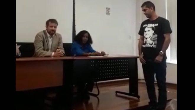 Imagem de vídeo que mostra o coordenador do curso de Segurança Pública da UFF tentando impedir um aluno com uma camiseta pró-Bolsonaro de fazer o juramento em sua formatura.