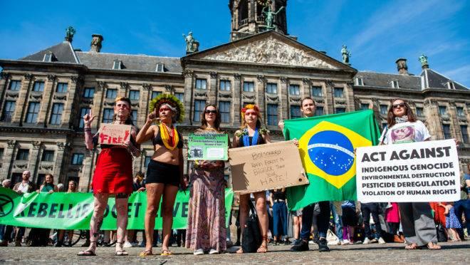 Manifestantes seguram cartazes contra políticas ambientais do governo brasileiro em Amsterdã, Holanda